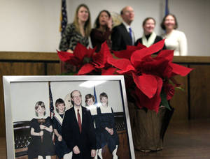 Photo - An old family photo is pictured in the foreground as Corporation Commissioner Bob Anthony poses with his daughters Thursday following his swearing-in at the Jim Thorpe Building in Oklahoma City. Photos by Sarah Phipps, The Oklahoman