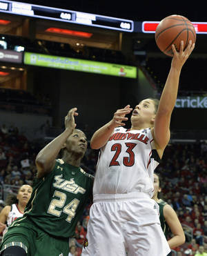 Photo - Louisville's Shoni Schimmel, right, shoots over the defense of South Florida's Alisia Jenkins during the first half of an NCAA college basketball game on Sunday Feb. 2, 2014, in Louisville, Ky. (AP Photo/Timothy D. Easley)