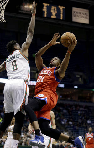 Photo - Philadelphia 76ers' Thaddeus Young (21) shoots against Milwaukee Bucks' Larry Sanders (8) during the first half of an NBA basketball game, Tuesday, Jan. 22, 2013, in Milwaukee. (AP Photo/Jeffrey Phelps)