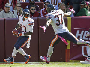 Photo - Chicago Bears wide receiver Devin Hester turns and looks at his teammate free safety Anthony Walters after scoring this 19th touchdown on a kickoff return during the first half of a NFL football game against the Washington Redskins in Landover, Md., Sunday, Oct. 20, 2013. (AP Photo/Alex Brandon)