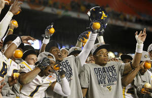 Photo - West Virginia has won 70 games in the last seven seasons and has won three straight major bowls, including a 70-33 romp over Clemson in the 2012 Orange Bowl. AP ARCHIVE PHOTO