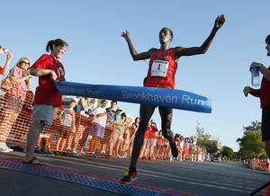 Photo - Silas Kisorio is the first-place finisher of the 5K event Saturday at the Brookhaven Run, held annually at 36th Avenue NW and Robinson Street to raise money for high school cross country programs. PHOTOS BY STEVE SISNEY, THE OKLAHOMAN
