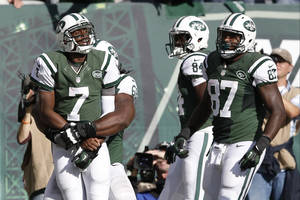 Photo - New York Jets quarterback Geno Smith (7) celebrates with teammates after scoring a touchdown during the second half of an NFL football game against the New England Patriots on Sunday, Oct. 20, 2013, in East Rutherford, N.J.  (AP Photo/Kathy Willens)
