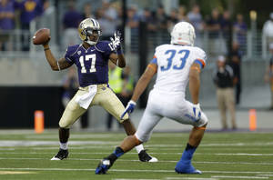Photo - Washington quarterback Keith Price (17) looks to pass around Boise State's Gabe Perez (33) in the first half of a NCAA college football game, Saturday, Aug. 31, 2013, in Seattle. (AP Photo/Ted S. Warren)