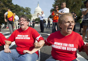 Photo - Women link arms and sit in a circle Thursday to block the intersection of Independence Avenue SE and New Jersey Avenue SE outside the House of Representatives on Capitol Hill in Washington. They were protesting Congress' inaction on comprehensive and inclusive immigration reform. AP Photo