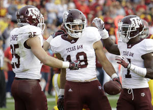 Photo - Texas A&M tight end Michael Lamothe, center, celebrates with teammates Ryan Swope, left, and Uzoma Nwachukwu after catching a touchdown pass during the first half of an NCAA college football game against Iowa State, Saturday, Oct. 22, 2011, in Ames, Iowa. (AP Photo/Charlie Neibergall) ORG XMIT: IACN103