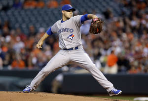 Photo - Toronto Blue Jays starting pitcher Dustin McGowan throws to the Baltimore Orioles in the first inning of a baseball game, Friday, April 11, 2014, in Baltimore. (AP Photo/Patrick Semansky)
