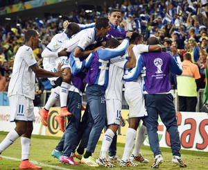 Photo - Honduras' Carlo Costly celebrates with teammates after scoring the opening goal during the group E World Cup soccer match between Honduras and Ecuador at the Arena da Baixada in Curitiba, Brazil, Friday, June 20, 2014.  (AP Photo/Martin Meissner)