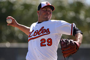 Photo - FILE - In this March 8, 2014 file photo, Baltimore Orioles relief pitcher Tommy Hunter throws in the fourth inning of an exhibition spring training baseball game against the Boston Red Sox in Sarasota, Fla. Hunter knows there will come a time this season when he blows a ninth-inning lead to turn a potential victory into a frustrating defeat. The manner in which the right-hander reacts to that disappointment could go a long way toward determining his success as the Baltimore Orioles' new closer. (AP Photo/Gene J. Puskar, File)