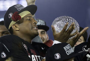 Photo - Florida State's Jameis Winston with The Coaches' Trophy after the NCAA BCS National Championship college football game against Auburn Monday, Jan. 6, 2014, in Pasadena, Calif. Florida State won 34-31. (AP Photo/David J. Phillip)