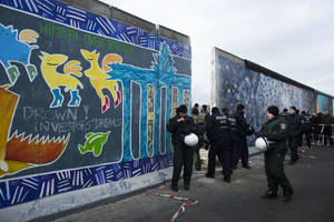 photo - German police officers protect a part of the former Berlin Wall in Berlin, Germany, Friday, March 1, 2013. Construction crews stopped work Friday on removing a small section from one of the few remaining stretches of the Berlin Wall to make way for a condo project after hundreds of protesters blocked their path. (AP Photo/Markus Schreiber)