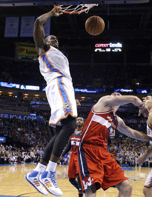 Photo - Oklahoma City's Serge Ibaka (9) dunks over Washington's Marcin Gortat (4) during the NBA game between the Oklahoma City Thunder and the Washington Wizards at the Chesapeake Energy Arena, Sunday, Nov. 10, 2013. Photo by Sarah Phipps, The Oklahoman