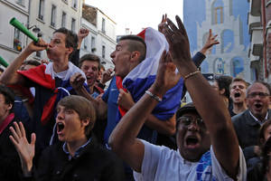 Photo - French soccer supporters react after the first goal as they watch a live broadcast of the group E World Cup soccer match between Switzerland and France, in the Metro 14th District bar in Paris, France, Friday, June 20, 2014. The match ended in a 5-2 win for France. (AP Photo/Francois Mori)