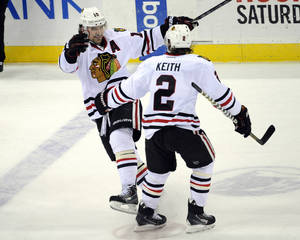 Photo - Chicago Blackhawks' Patrick Sharp celebrates his hat trick with Duncan Keith (2) during the third period of an NHL hockey game against the New Jersey Devils, Friday, Jan. 3, 2014, in Newark, N.J.  The Blackhawks won 5-3. (AP Photo/Bill Kostroun)