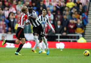 Photo - Newcastle United's captain Cheick Tiote, right, vies for the bal with Sunderland's Seb Larsson, left, during their English Premier League soccer match at the Stadium of Light, Sunderland, England, Sunday, Oct. 27, 2013. (AP Photo/Scott Heppell)