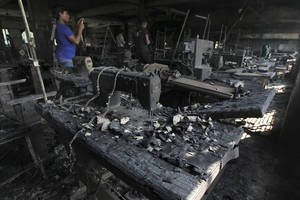photo -   A man takes photographs inside a garment-factory where a fire killed more than 110 people Saturday on the outskirts of Dhaka, Bangladesh, Monday, Nov. 26, 2012. Bangladeshi workers protested blocks from the gutted fire Monday, demanding justice for the victims and improved safety. Some 200 factories were closed for the day after the protest erupted in Savar, a suburb of Dhaka, the capital. (AP Photo)  