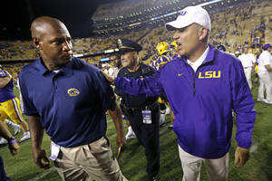 Photo - LSU head coach Les Miles, right, greets Kent State head coach Paul Haynes after an NCAA college football game in Baton Rouge, La., Saturday, Sept. 14, 2013. LSU won 45-13. (AP Photo/Gerald Herbert)