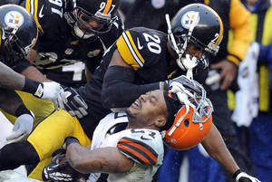 Photo - Cleveland Browns running back Edwin Baker (27) loses his helmet as he is tackled by Pittsburgh Steelers strong safety Will Allen (20) in the third quarter of an NFL football game on Sunday, Dec. 29, 2013, in Pittsburgh. The Steelers won 20-7. (AP Photo/Don Wright)