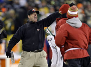 Photo - San Francisco 49ers head coach Jim Harbaugh directs his team during the first half of an NFL wild-card playoff football game against the Green Bay Packers, Sunday, Jan. 5, 2014, in Green Bay, Wis. (AP Photo/Mike Roemer)