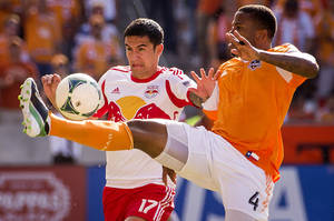 Photo - Houston Dynamo defender Jermaine Taylor (4) fights for the ball against New York Red Bulls midfielder Tim Cahill (17) during an MLS soccer match on Sunday, Oct. 20, 2013, at BBVA Compass Stadium in Houston. New York won the game 3-0.  (AP Photo/Houston Chronicle, Smiley N. Pool )