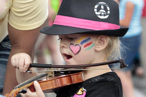 Photo - Skylar Allen, 3, tries out a violin in the children's area Saturday at the Norman Music Festival.