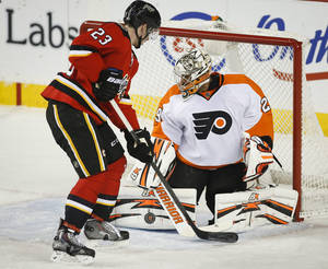 Photo - Philadelphia Flyers goalie Ray Emery, right, stops a shot from Calgary Flames' Sean Monahan during the second period of an NHL hockey game in Calgary, Alberta, Tuesday, Dec. 31, 2013. (AP Photo/The Canadian Press, Jeff McIntosh)