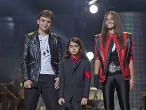 "Photo -   FILE - In this Oct. 8, 2011 file photo, from left, Prince Jackson, Prince Michael II ""Blanket"" Jackson and Paris Jackson arrive on stage at the Michael Forever the Tribute Concert, at the Millennium Stadium in Cardiff, Wales. TJ Jackson, one of Michael's favorite nephews, has been designated to work beside Michael's mother, Katherine, to look after the welfare of his three cousins Prince, 15, Paris, 14 and Blanket,10, who will inherit the King of Pop's fortune. (AP Photo/Joel Ryan, File) *Editorial Use Only*"