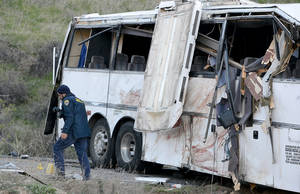 Photo - Authorities work Monday Feb. 4, 2013, at the scene of Sunday's fatal tour bus crash on Highway 38 north of Yucaipa, Calif., that left at least eight people dead and dozens injured. The cause of the Sunday crash east of Los Angeles remained under investigation. (AP Photo/The Sun, Rick Sforza)