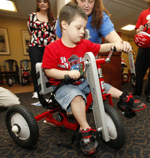 Photo - Sheena Patterson assists her son, Xavier Skadas, 5, as he tries out his new AmTryke donated by Edmond AMBUCS. PHOTOS BY PAUL HELLSTERN, THE OKLAHOMAN