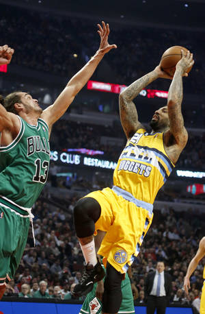 Photo - Denver Nuggets guard Wilson Chandler (21) shoots over Chicago Bulls center Joakim Noah (13) during the first half of an NBA basketball game, Monday, March 18, 2013, in Chicago. (AP Photo/Charles Rex Arbogast)