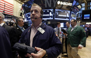 Photo -  Trader James Doherty, center, works on the floor of the New York Stock Exchange.    AP File Photo <strong>Richard Drew -  AP </strong>