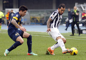 Photo - Juventus' Carlos Tevez, right, of Argentina, is chased by Verona's Juan Manuel Iturbe, of Paraguay, during a Serie A soccer match at Bentegodi stadium in Verona, Italy, Sunday, Feb. 9, 2014. (AP Photo/Felice Calabro')