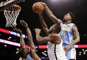 Photo - Denver Nuggets forward Wilson Chandler (21) strips the ball from Brooklyn Nets center Andray Blatche, center, in the first half of an NBA basketball game Tuesday, Dec. 3, 2013, in New York. (AP Photo/Kathy Willens)