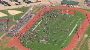 "Photo - In this image from video provided by KHOU, students evacuated from Seven Lakes High School in Katy, Texas, mingle on the football field on Monday Jan. 13, 2014 after officials say a ""potential explosive device"" was identified in the building. After a bomb squad was dispatched, a student is in custody. (AP Photo/KHOU)"