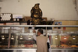 Photo -   In this April 10, 2012, photo, a man looks at the buffet line at a restaurant in the Chinatown section of Los Angeles. When Walmart announced plans to put one of its sprawling outlets in Chinatown, alarms were quickly sounded by people fearful that a chain superstore would destroy the character of one of the nation's oldest, largest and most historic Chinatowns. These days New Chinatown, as it was called then, finds itself increasingly surrounded by multi-ethnic neighborhoods and high-density residential developments like the building that would house the Walmart store on its ground floor. (AP Photo/Jae C. Hong)