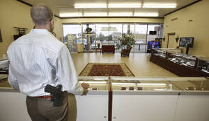 Photo - At right: Michael Butler stands guard with his gun exposed at Absolute Diamond & Gold Buyers in Oklahoma City. The business is one of several that will continue to allow its employees and customers to carry their weapon concealed Thursday but will advise against open carry. Photo by Steve Gooch,  The Oklahoman
