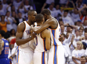 Photo -  Oklahoma City's Serge Ibaka (9) and Kevin Durant (35) hug Russell Westbrook (0) after he was fouled on a 3-point shot late in the fourth quarter during Game 5 of the Western Conference semifinals in the NBA playoffs between the Oklahoma City Thunder and the Los Angeles Clippers at Chesapeake Energy Arena in Oklahoma City, Tuesday, May 13, 2014. Photo by Sarah Phipps, The Oklahoman