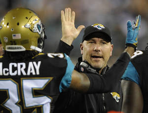 Photo - Jacksonville Jaguars head coach Gus Bradley high fives cornerback Demetrius McCray (35) after a play against the Houston Texans during the second quarter of an NFL football game Thursday, Dec. 5, 2013, in Jacksonville, Fla. (AP Photo/Stephen Morton)