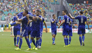 Photo - Bosnia's Avdija Vrsajevic is carried by a teammate as he celebrates after scoring his team's third goal during the group F World Cup soccer match between Bosnia and Iran at the Arena Fonte Nova in Salvador, Brazil, Wednesday, June 25, 2014. (AP Photo/Martin Mejia)