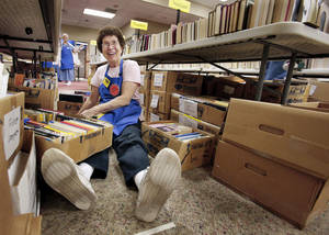 Photo - Volunteer Barbara Cooper sorts books for the Friends of the Norman Library book sale that starts Friday.  PHOTO BY STEVE SISNEY, THE OKLAHOMAN