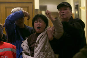 "Photo - A relative of one of the Chinese passengers aboard the Malaysia Airlines, MH370 grieves after being told of the latest news in Beijing, China, Monday, March 24, 2014. A new analysis of satellite data indicates the missing Malaysia Airlines plane crashed into a remote corner of the Indian Ocean, Malaysian Prime Minister Najib Razak said Monday. Malaysia Airlines said in a statement to the families that ""our prayers go out to all the loved ones of the 226 passengers and of our 13 friends and colleagues at this enormously painful time."" (AP Photo/Ng Han Guan)"