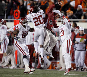 Photo - Oklahoma's Frank Alexander (84), Oklahoma's Quinton Carter (20) and Marcus Trice (13) celebrate a interception with a coach during the Bedlam college football game between the University of Oklahoma Sooners (OU) and the Oklahoma State University Cowboys (OSU) at Boone Pickens Stadium in Stillwater, Okla., Saturday, Nov. 27, 2010. Photo by Sarah Phipps, The Oklahoman