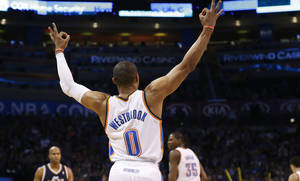 Photo - Oklahoma City Thunder guard Russell Westbrook (0) signals a three-point basket by teammate Kevin Durant (35) in the first quarter of an NBA basketball game against the Utah Jazz in Oklahoma City, Sunday, March 30, 2014. (AP Photo/Sue Ogrocki)