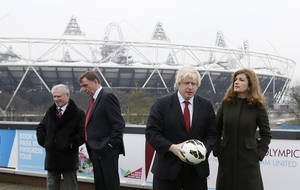 Photo - Mayor of London Boris Johnson, second right,  with Karen Brady, vice chairman of  English Premier League soccer team West Ham United,  pose for the media on a balcony overlooking the London 2012 Olympic summer games stadium London, Friday, March, 22, 2013. The stadium built for the summer games has had its future secured in a deal where a local English Premier League team West Ham United will have a 99 year lease to use the stadium starting in 2016, it was announced at a press conference in  (AP Photo/Alastair Grant)