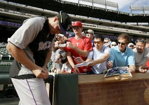 Photo - Colorado Rockies' Nolan Arenado signs autographs for fans during batting practice before a baseball game against the Texas Rangers, Wednesday, May 7, 2014, in Arlington, Texas. (AP Photo/Tony Gutierrez)