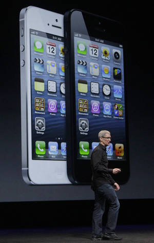 photo -   Apple CEO Tim Cook speaks in front of an image of the iPhone 5 during an Apple event in San Francisco, Wednesday, Sept. 12, 2012. (AP Photo/Jeff Chiu)