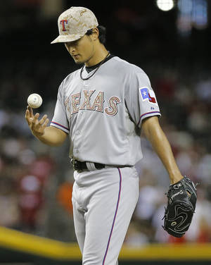 Photo - Texas Rangers pitcher Yu Darvish, of Japan, walks to the mound after giving up a base hit against the Arizona Diamondbacks during the sixth inning of an interleague baseball game, Monday, May 27, 2013, in Phoenix. (AP Photo/Matt York)