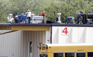 photo - Workers make repairs to a hail damaged roof recently at the Oklahoma City Public Schools service center in northeast Oklahoma City. Hailstorms in 2010 and 2012 damaged dozens of buildings throughout the school district. Photo by Steve Gooch, The Oklahoman <strong>Steve Gooch</strong>