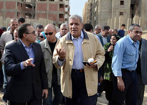 Photo - In this Nov. 24, 2013 photo, Ibrahim Mehlib, center, tours a government housing project in Ismailiya, Egypt. Egypt's interim president has chosen as prime minister a construction magnate from the era of ousted autocrat Hosni Mubarak. Adly Mansour on Tuesday, Feb. 25, 2014 named Mehlib, who had for more than a decade led Egypt's biggest construction company, Arab Contractors, to replace Hazem el-Beblawi, who resigned on Monday.(AP Photo/Khaled Kandil)