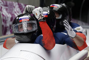 Photo - The team from Russia RUS-1, with Alexander Zubkov, Alexey Negodaylo, Dmitry Trunenkov, and Alexey Voevoda, brake in the finish area after tenor second run during the men's four-man bobsled competition at the 2014 Winter Olympics, Saturday, Feb. 22, 2014, in Krasnaya Polyana, Russia. (AP Photo/Michael Sohn)